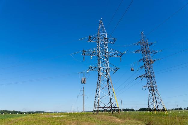 Линии электропередач высокого напряжения против голубого неба. Premium Фотографии