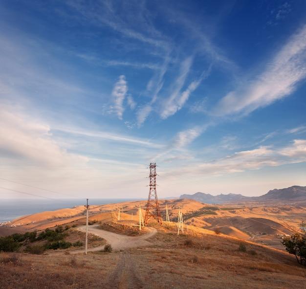 Башня высокого напряжения в горах на закате Premium Фотографии