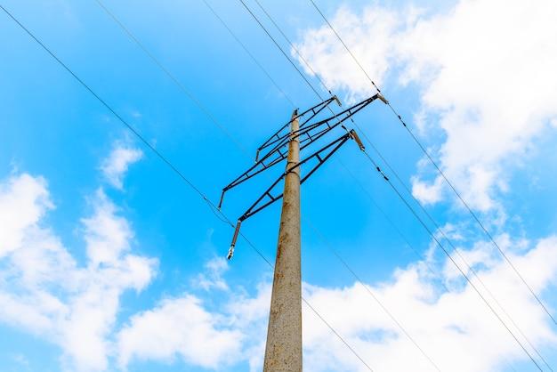 Лэп высокого напряжения с бетонными опорами, голубое небо. электрическая система Premium Фотографии