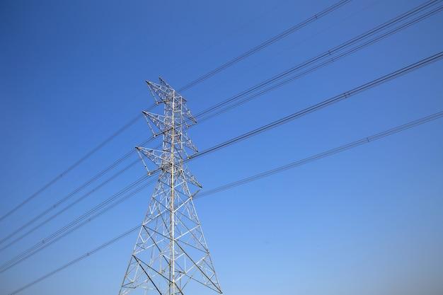 Башня высоковольтной передачи и проводка электрического напряжения на голубом небе Premium Фотографии