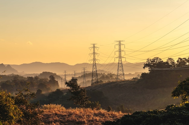 Башня передачи высокого напряжения на закате Premium Фотографии