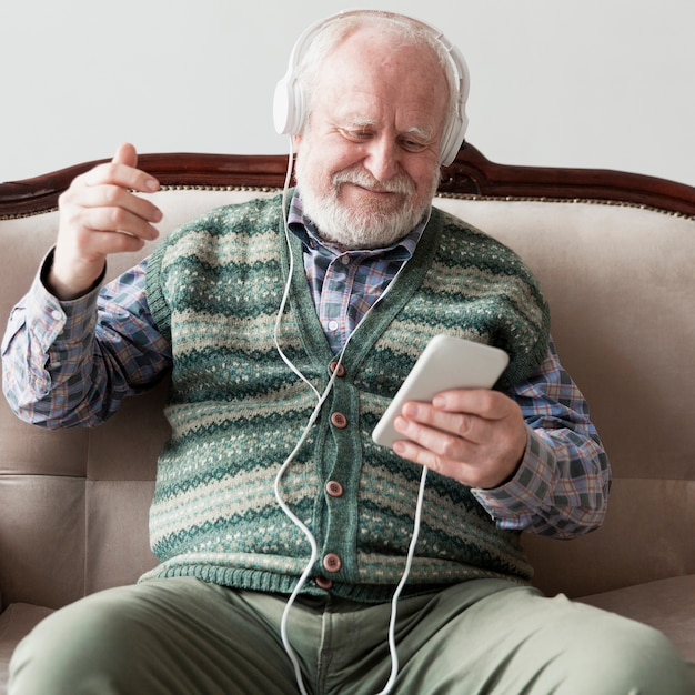 Higha ngle senior on couch playing songs Free Photo