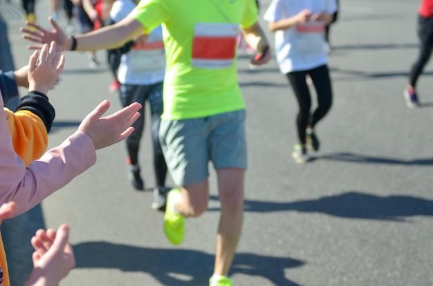 Марафонский забег, поддержка бегунов на дороге, рука ребенка раздает highfive Premium Фотографии