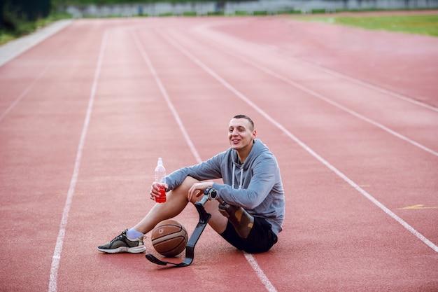 競馬場の上に座って、リフレッシュメントを保持しているスポーツウェアで非常にやる気のあるハンサムな白人スポーティな障害を持つ男。足の間はバスケットボールです。 Premium写真