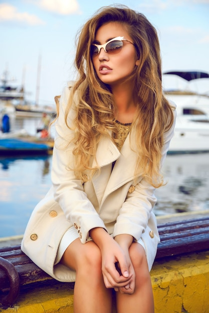 Hight fashion portrait of beautiful model with curled trendy ombre hairs, cozy autumn cream wool coat, golden top and sunglasses, amazing whew on awe port and yacht club. Free Photo