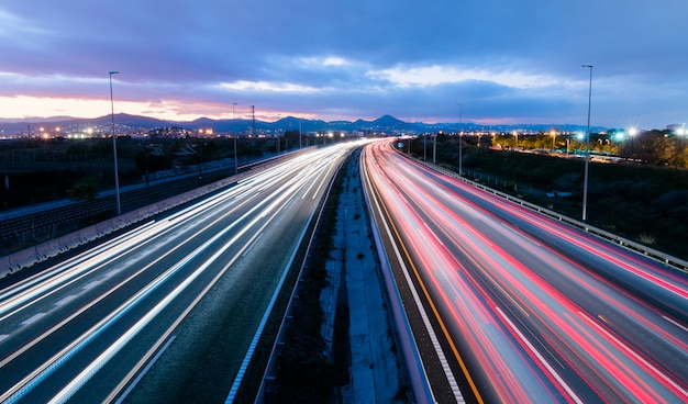 Highway at sunset, vehicles driving in two directions leaving trails of light Premium Photo