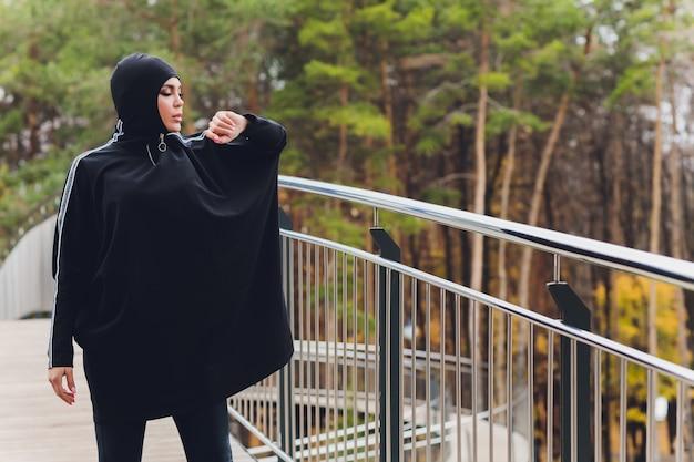 早朝に歩道橋にヒジャーブの女性 Premium写真