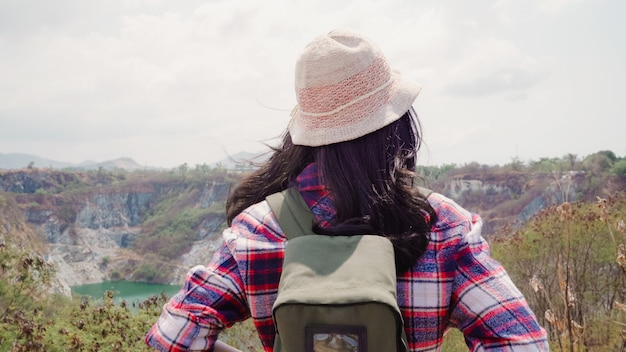 Hiker asian backpacker woman walking to top of mountain, female enjoy her holidays on hiking adventure feeling freedom. lifestyle women travel and relax in free time concept. Free Photo