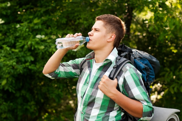 Hiker drinking water in forest Free Photo