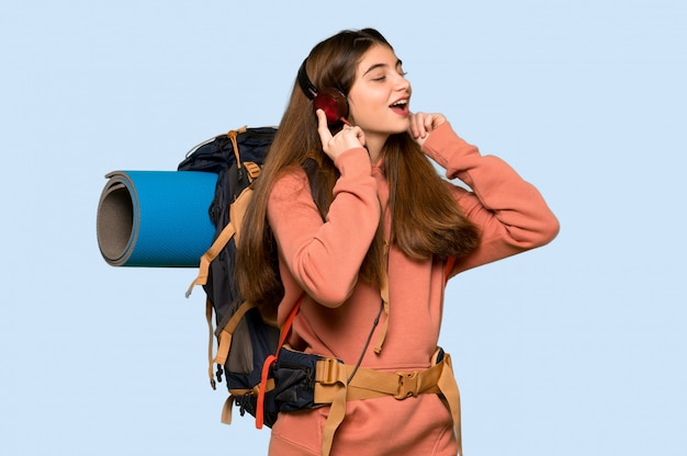 Hiker girl listening to music with headphones on on blue Premium Photo