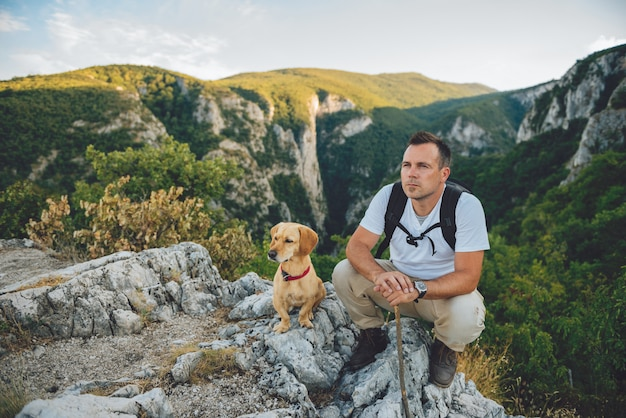 Hiker and his dog sitting on the mountain top Premium Photo