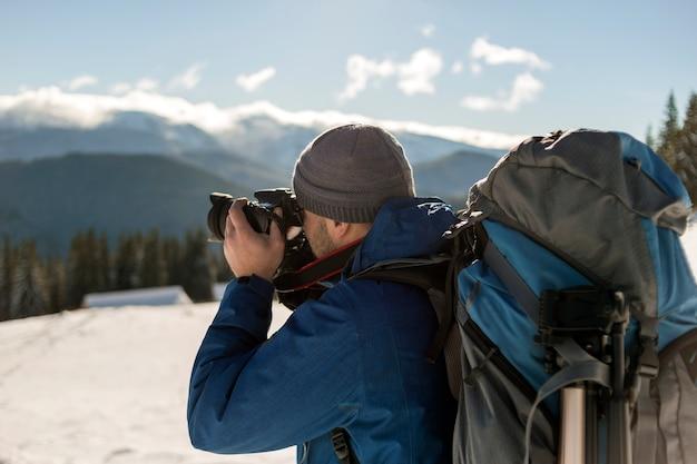 Турист-фотограф человек-путешественник в теплой одежде с рюкзаком и камерой, фотографирующий снежную долину и лесные горные вершины под голубым небом в солнечный зимний холодный день. Premium Фотографии