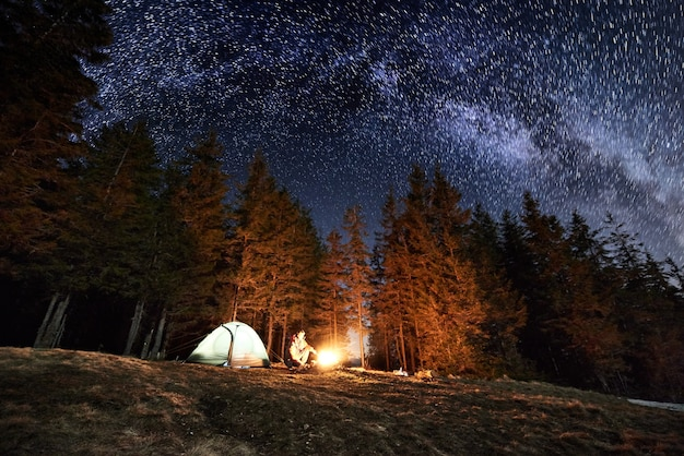 Путешественник возле костра и туристической палатки ночью Premium Фотографии
