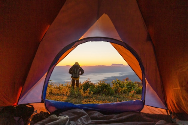 Hiker stand at the camping near orange tent and backpack in the mountains Free Photo