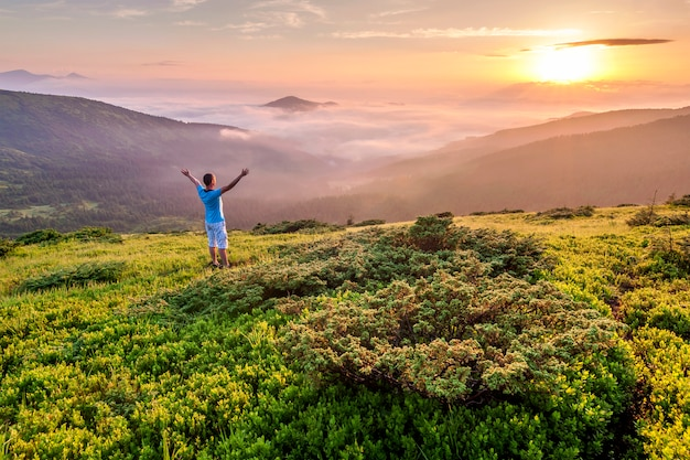 Hiker standing on top of a mountain with raised hands and enjoying sunrise Premium Photo