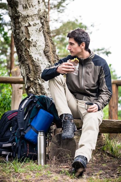 Hiker taking food break in shade of tree Premium Photo