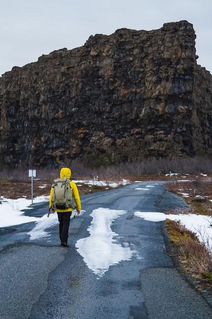Escursionista in una giacca gialla che cammina attraverso la strada circondata da rocce e un campo in islanda Foto Gratuite