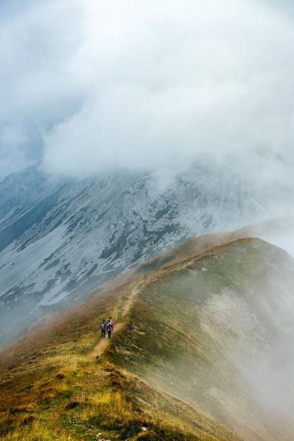 Escursionisti che salgono un sentiero di montagna Foto Gratuite