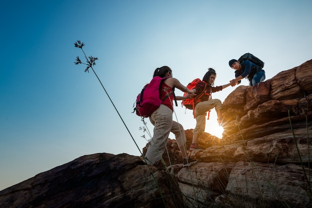 Hikers walking with backpack on a mountain at sunset. traveler going camping. travel concept. Premium Photo