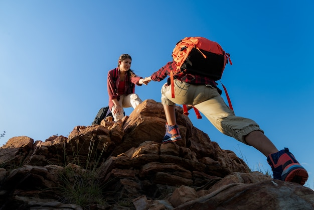 Hikers walking with backpack on a mountain at sunset. traveler going camping Premium Photo