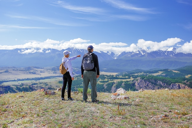 Hikers with backpacks relaxing on top of a mountain. travel happy emotions lifestyle concept.  family traveling active adventure vacations Premium Photo