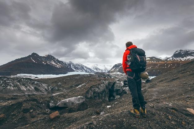 アイスランドの氷河を見ているハイキング冒険旅行の男。 無料写真