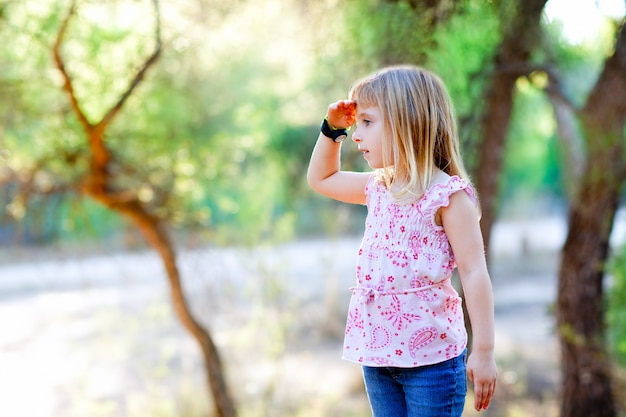 Hiking kid girl searching hand in head in forest Premium Photo
