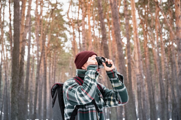 Hiking male person in winter forest taking photograph. man in checkered winter shirt in beautiful snowy woods uses old film camera Premium Photo