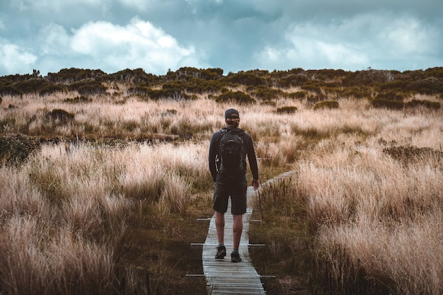 A hiking man walking on the pathway with yellow grass on a high mountain. cloudy and shower rain scene. Premium Photo