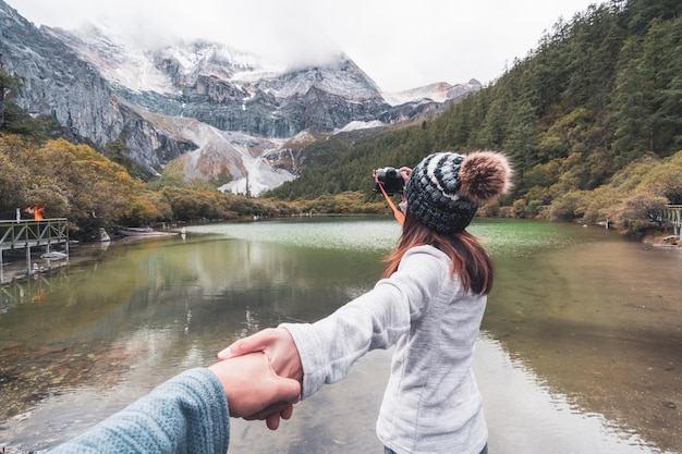 Hiking young couple traveler looking beautiful landscape at yading nature reserve, travel lifestyle concept Premium Photo