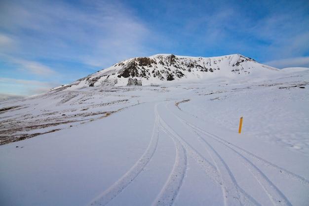 アイスランドの冬の間、日光と青い空の下で雪に覆われた丘 無料写真