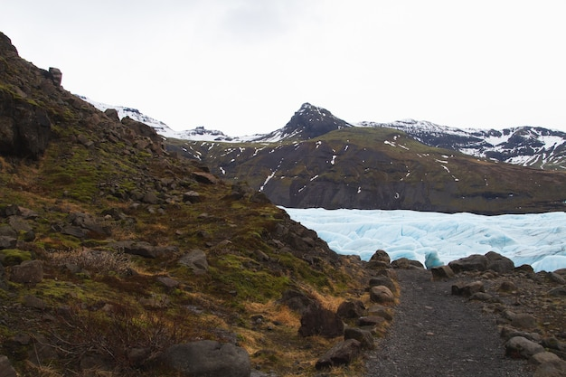 Hills covered in the snow and grass surrounded by a frozen lake in vatnajokull national park Free Photo