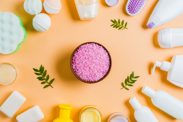 Himalayan salt bowl with cosmetics products on colored background Free Photo