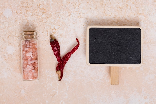 Himalayan salt; chili pepper and blank placard on textured backdrop Free Photo
