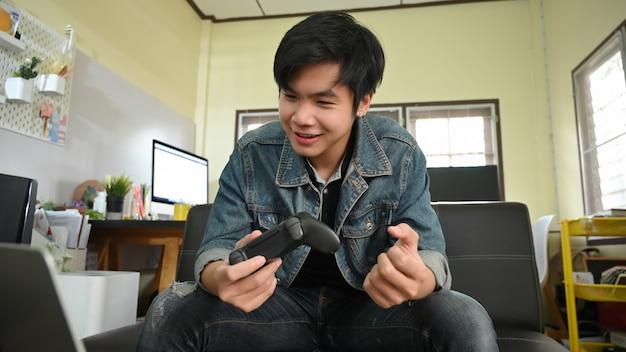 ビデオゲームをプレイし、ジョイスティックを手に持って、自宅の快適なリビングルーム.himselfの上の革のソファに座っているスマートな男の写真。 Premium写真