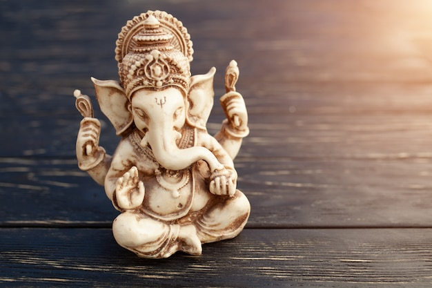 Hindu god ganesh on black background. statue on wooden table Premium Photo