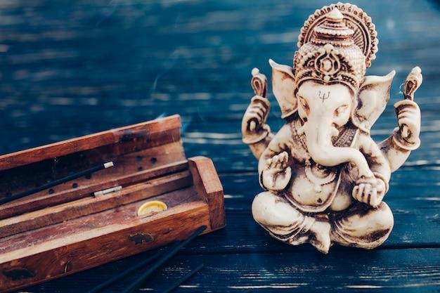 Hindu god ganesh on black background. statue on wooden table Premium Photo