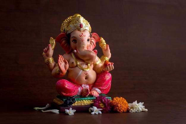 ヒンドゥー教の神ガネーシャ。暗い木の空間にガネーシャアイドル。 Premium写真