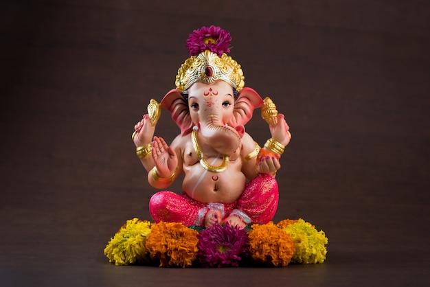 ヒンドゥー教の神ガネーシャ。暗い木製のテーブルにガネーシャアイドル。 Premium写真