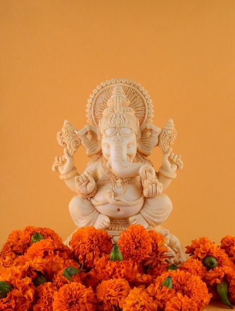 ヒンドゥー教の神ガネーシャ。黄色の背景にガネーシャアイドル Premium写真