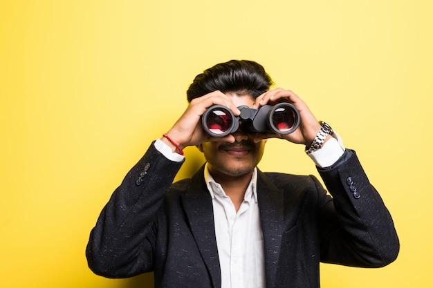 Hindu young man with binoculars isolated on yellow wall Free Photo