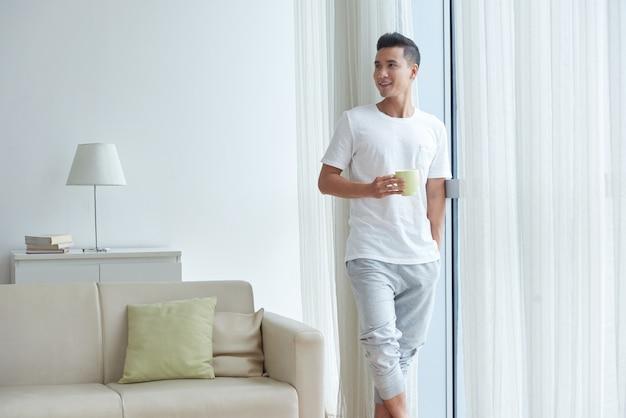 パン窓に立っているお茶を一杯とhiomeで朝を楽しんでいる若い男の肖像 無料写真