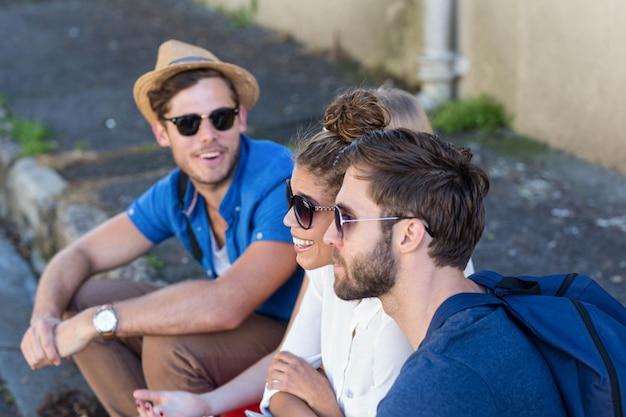 Hip friends sitting on sidewalk in the city Premium Photo