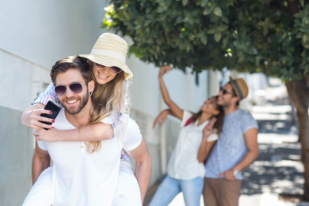 Hip man giving piggy back to his girlfriend and taking selfie on the street Premium Photo
