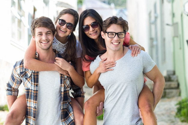 Hip men giving piggy back to their girlfriends on the street Premium Photo