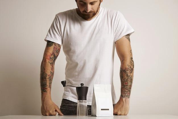 Бариста с татуировкой на бедре в простой белой футболке смотрит на небольшую ручную кофемолку и немаркированный белый пакет с кофейными зернами Бесплатные Фотографии