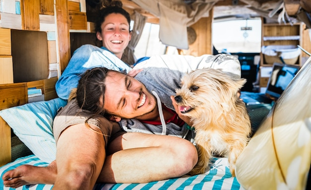 Hippie couple with funny dog traveling together on vintage minivan transport Premium Photo