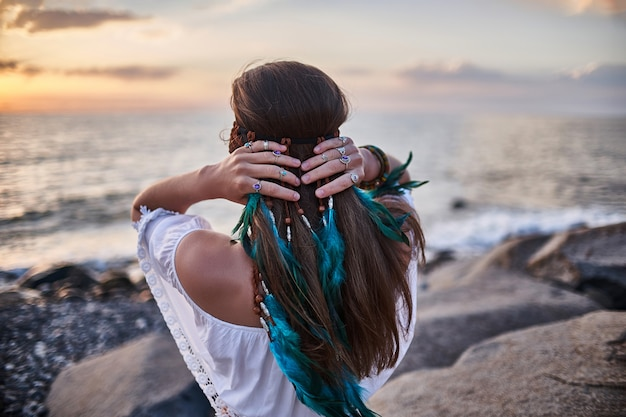 Hippie indie girl with blue feathers in hair Premium Photo