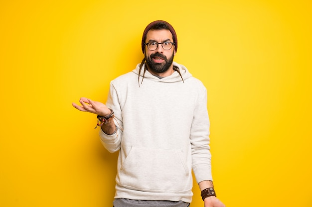 Hippie man with dreadlocks unhappy and frustrated with something because not understand something Premium Photo