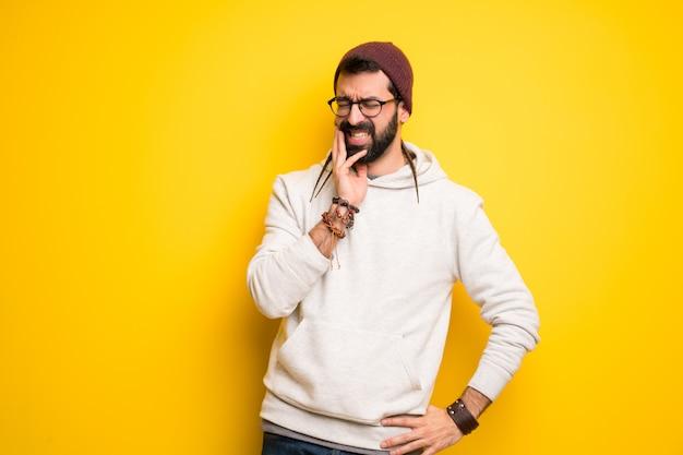 Hippie man with dreadlocks with toothache Premium Photo